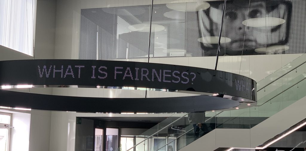 "Image of digital sign reading ""what is fairness?"""