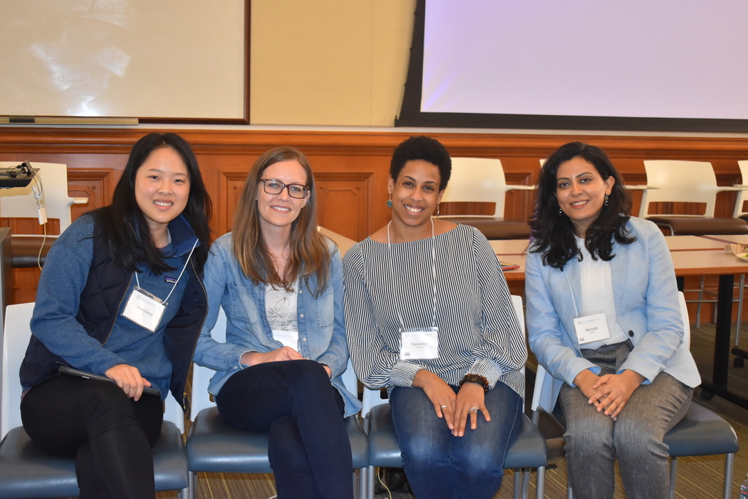 Four CTSP alumni, all women, women sitting and posing for the camera with smiles.